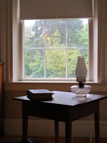 Mesa de trabalho perto da janela do quarto de Emily Dickinson